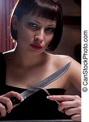 woman in a black dress with a knife - beautiful woman in a...