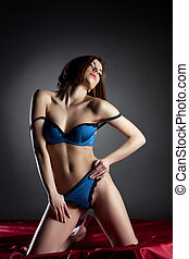 Young sexy woman in blue lingerie posing on red