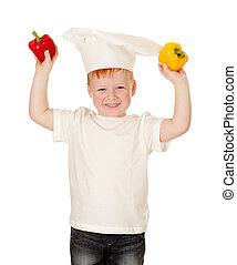 boy in cooking hat with vegetables Kid helping in food...