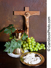 Holy communion image showing a golden chalice with grapes...
