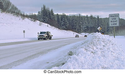 Winter Road Traffic Snowy Downhill - Several vehicles being...