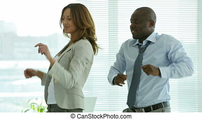 Office dancing - Two smiling businesspeople dancing...