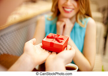Present - Close-up of man giving red giftbox to happy girl