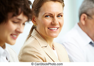 Leadership - Smiling business woman looking at camera among...