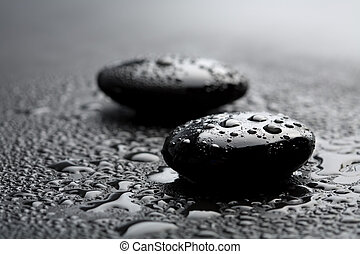 black shiny zen stones with water drops over black...