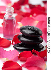 spa stones, essential oil and rose petals
