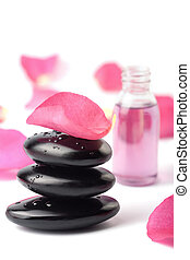 spa stones, essential oil and rose petals isolated