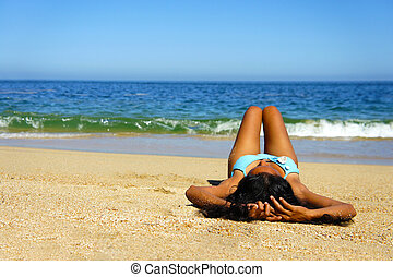 Woman Sun Tanning - Young woman laying on beach sun tanning...