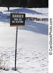Danger Thin Ice - Sign on edge of frozen pond warning of...