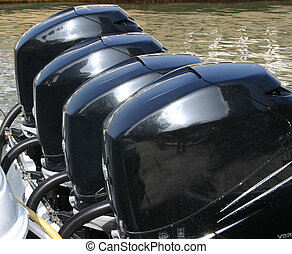 Boat Motors - A line of four boat motors on the back of a...