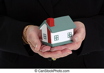 Woman Holding House - Senior woman holding a small house in...