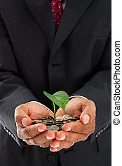 Man Holding Plant In Money - Hispanic man holding a plant in...