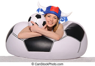 Happy football cheerleader with ball on couch