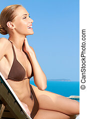 Cute woman sitting on sunbed and smiling - Cute young woman...