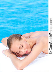 Woman during spa treatment next to pool