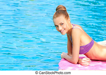 Young woman in swimsuit lying close to pool - Young woman in...