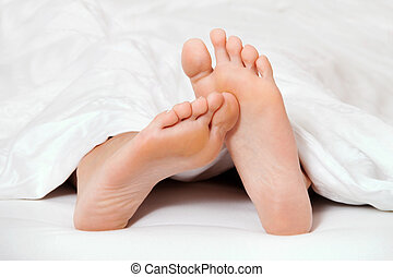 feet in bed - two feet in bed looking out from under a...