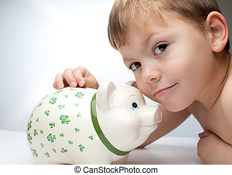 kid with a piggy bank - young child , boy saves change in...