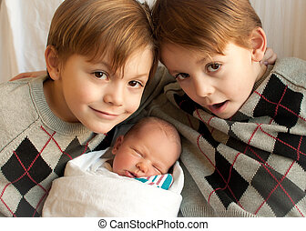 3 brothers - twin boys pose with a newborn baby brother in...