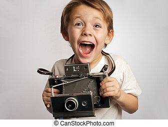 insant camera kid - young child holding a instant camera on...