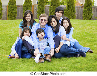 Large multiracial family of seven sitting together on lawn,...