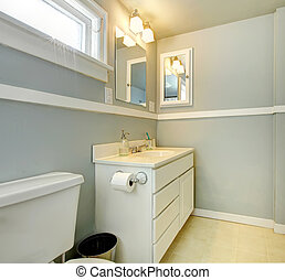 Grey bathroom with white simple cabinet.