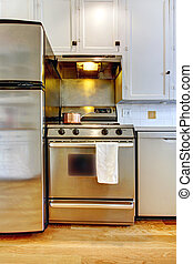 Stove and refrigerator in stainless steal with white kitchen.