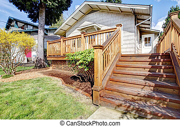 Small white house with deck and steps.