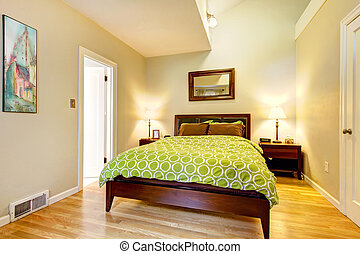 Modern green and beige bedroom with brown bed.