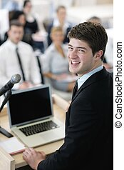 Young  business man giving a presentation on conference