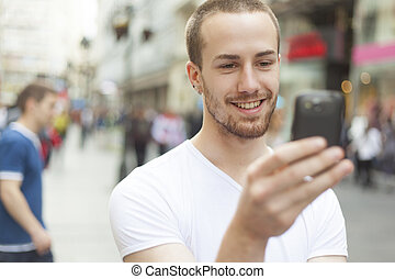 Young Man with cell phone walking - Young Man with mobile...
