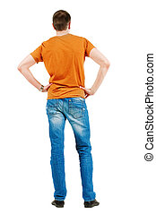 Back view of young men in orange t-shirt. Guy looks at wall....