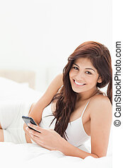 A woman holding her smartphone while she lies on the bed and smiling.