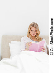 Closer shot, Woman reading her book while sitting in bed