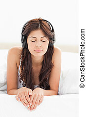 A woman with headphones on listening to music, her eyes...