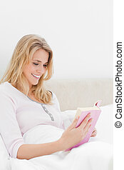 A close up side angle shot of a smiling woman who is in bed reading her book.