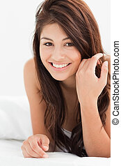A close up shot of a smiling woman looking forward while lying on the bed and brushing her hair slightly,