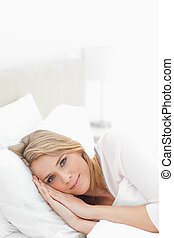 A woman resting in the bed, with her eyes open and her hands and head both resting on the pillow.