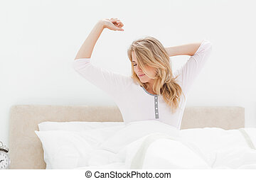 Woman in bed stretching as she wakes up from sleeping - A...