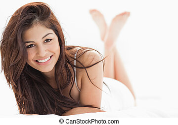A woman smiling with her crossed arms on the bed, her legs raised and crossed.