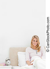 A Vertical shot of a smiling woman sitting in bed against the headboard with the alarm clock on a desk beside her.