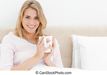 A woman sitting upright in bed, with a cup in her hands held...