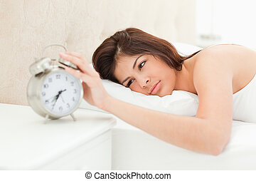 A woman lying on a bed with her hand on the bell of the nearby alarm clock to cease its ringing.