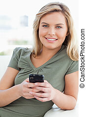 Woman looking forward and smiling as she holds her phone