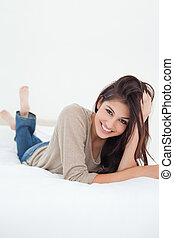 A close up shot of a woman lying on the bed with her feet raised slightly and her hand in her hair.