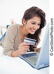 Close up , woman with credit card looking at laptop and...