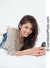 A smiling woman on her bed with her phone in her hands and looking forward.