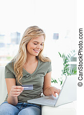 A woman on the couch, smiles as she holds her credit card and uses her laptop.