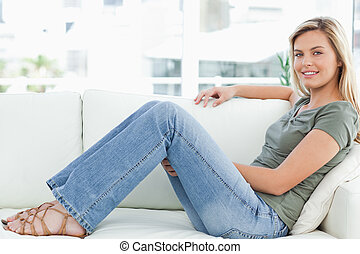 A woman sitting across the couch, an arm across the top of...