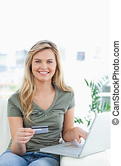 A woman on the couch smiles as she uses her laptop and credit card to order.